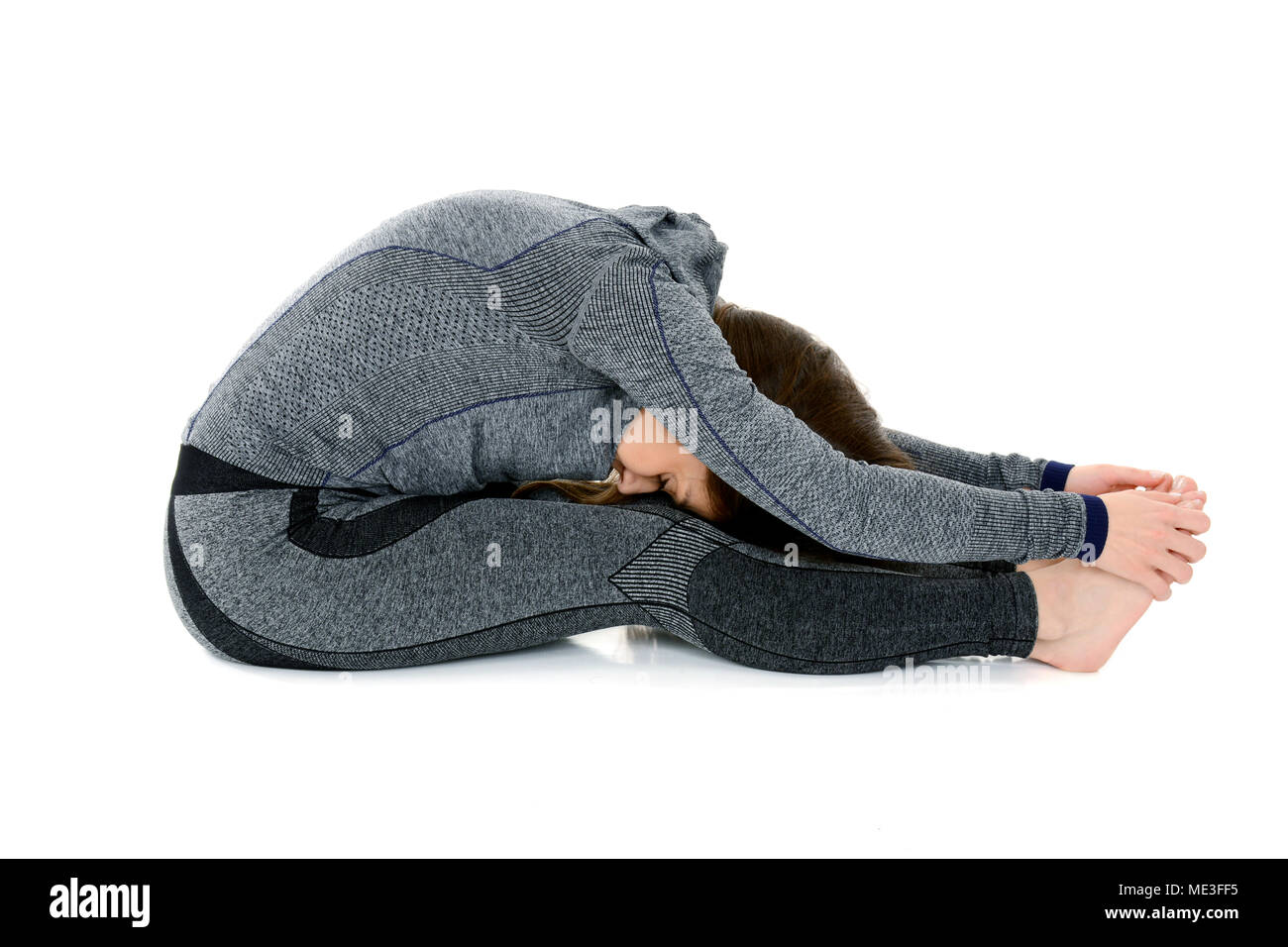 Young woman doing yoga asana Seated Forward Bend Paschimottanasana isolated on white background - Stock Image