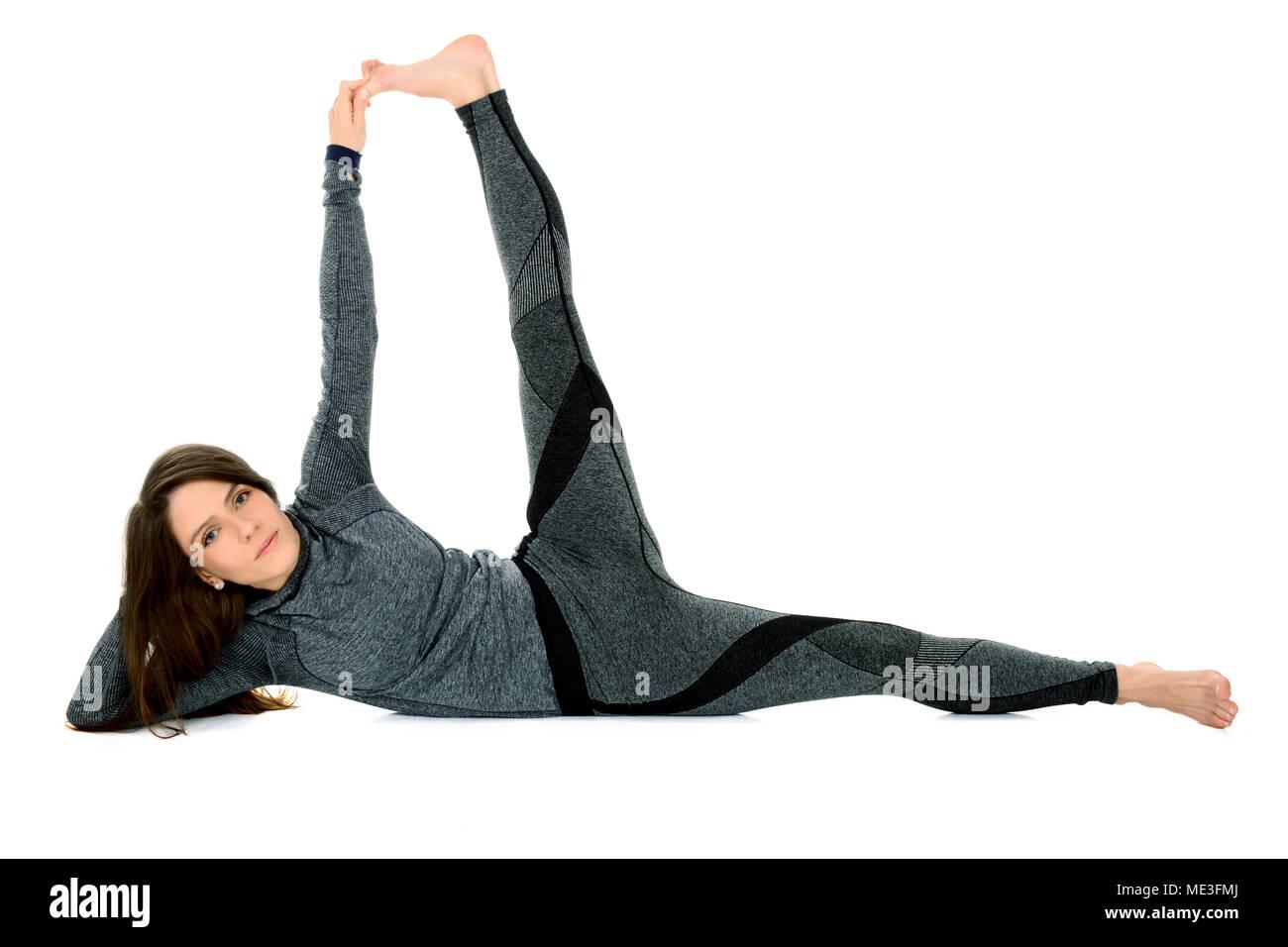 young woman doing yoga asana Anantasana Side-Reclining Leg Lift - Stock Image