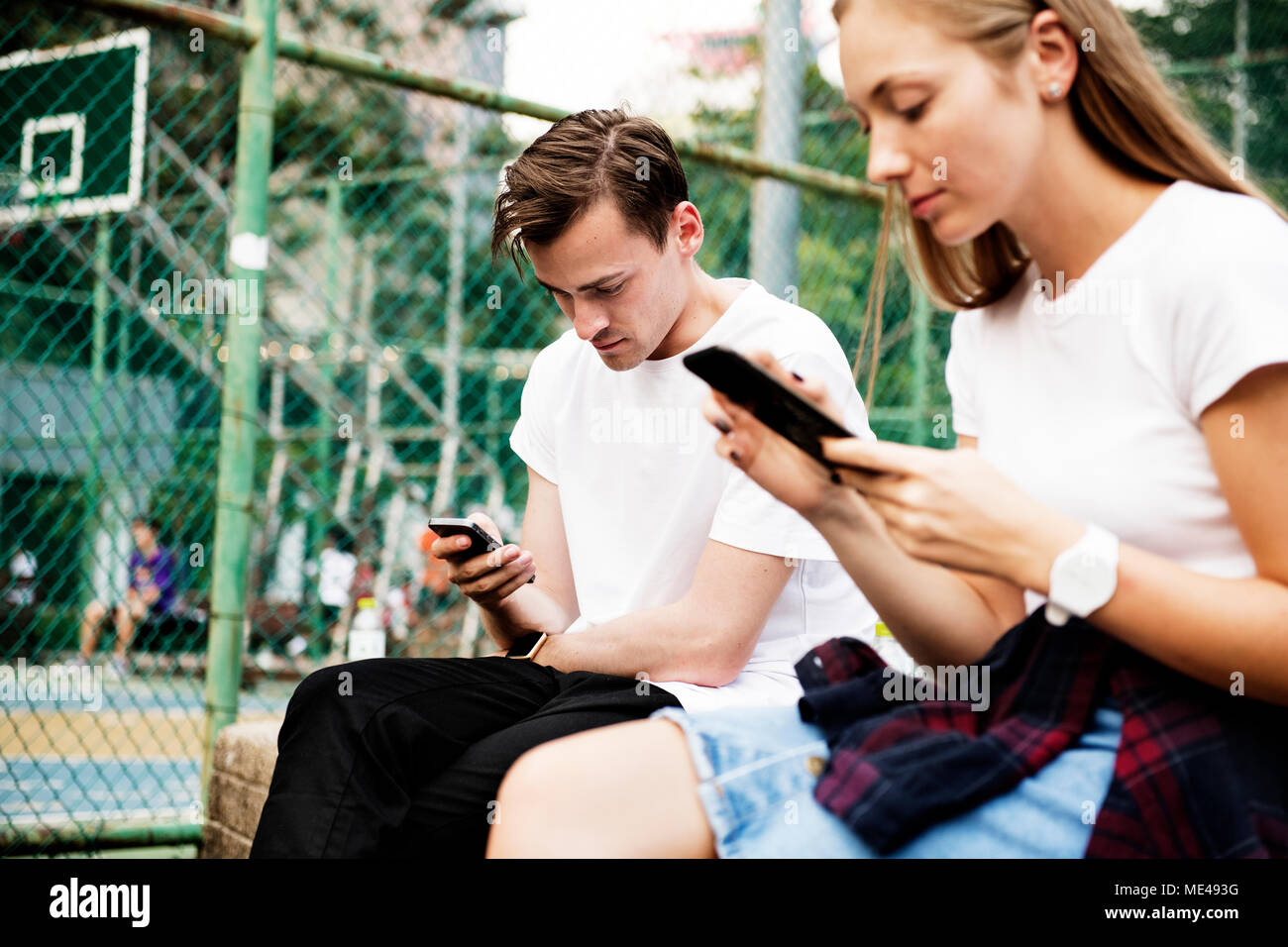 Expressionless young couple in the park using smartphones with no social interactions addiction concept - Stock Image