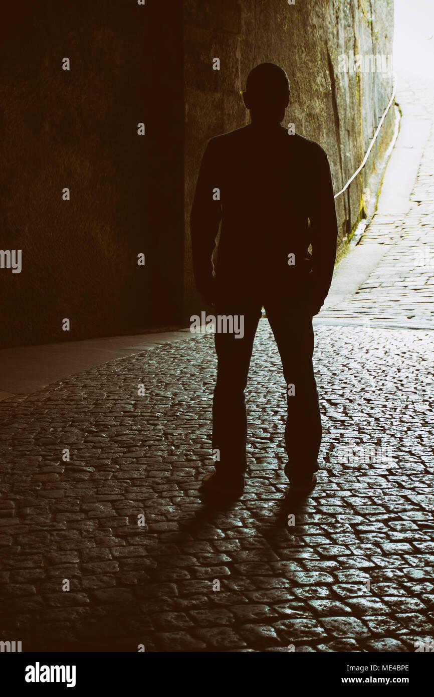 Rear view of a mysterious male figure standing on cobbled road - Stock Image