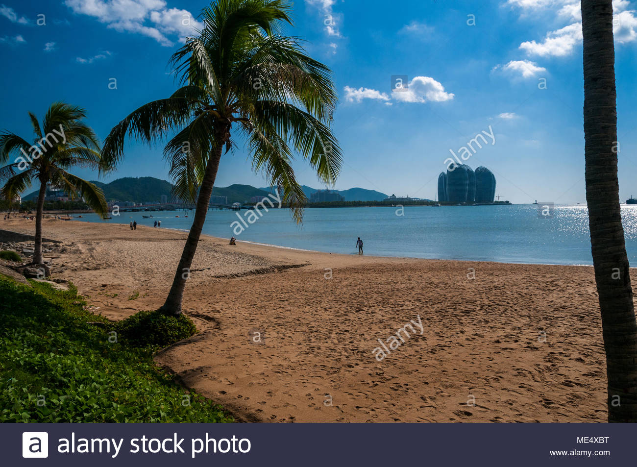 Beach in the main city part of Sanya with the buildings of Phoenix Island in the background. Hainan Island, China. - Stock Image