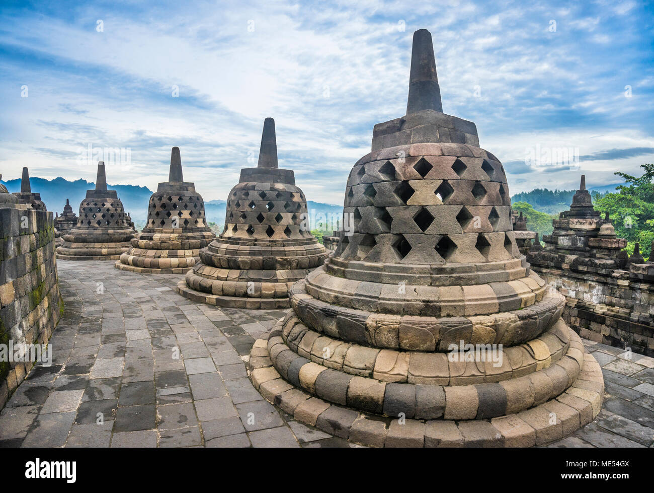 perforated stupas containing Buddha statues on the circular top terraces of 9th century Borobudur Buddhist temple, Central Java, Indonesia - Stock Image