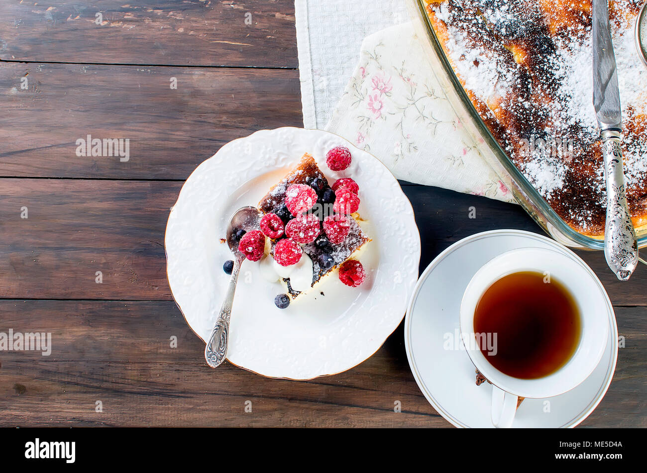 Portion cottage cheese casserole with  tea on a wooden table. health or diet concept.selective focus - Stock Image