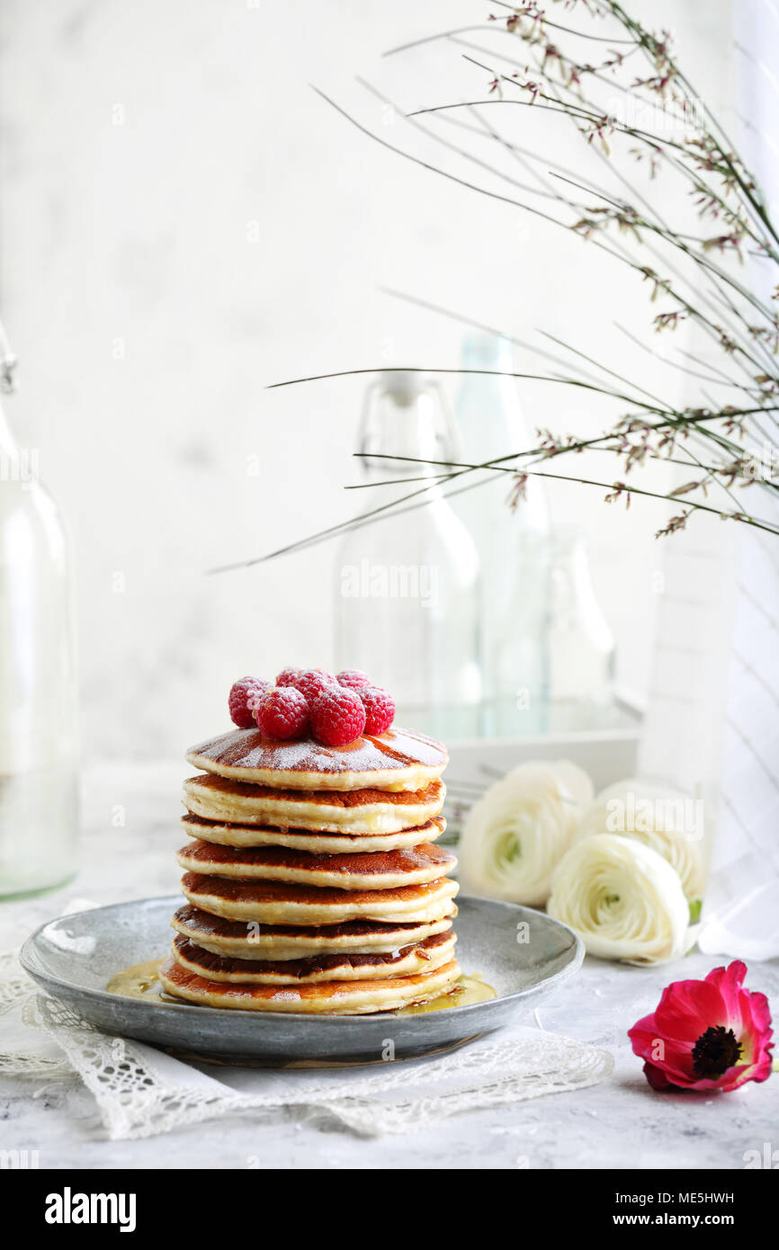 pile of pancakes sprinkled with powdered sugar decorated with raspberries - Stock Image