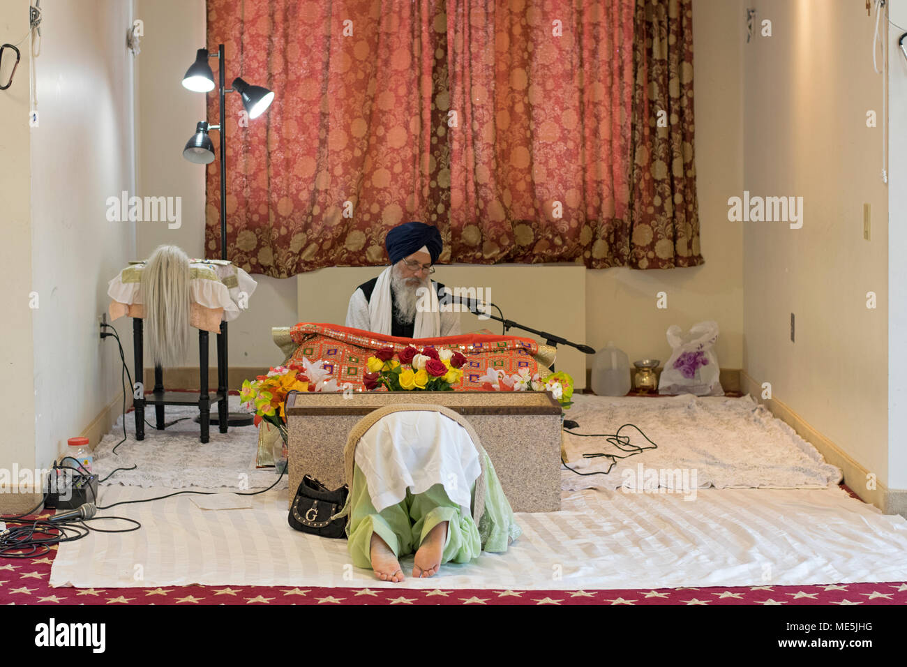 A woman bowing in front of a Sikh priest, a Granthi, who's reading Sri Guru Granth Sahib, the Holy Book in Sikhism. In Richmond Hill Queens, New York. - Stock Image