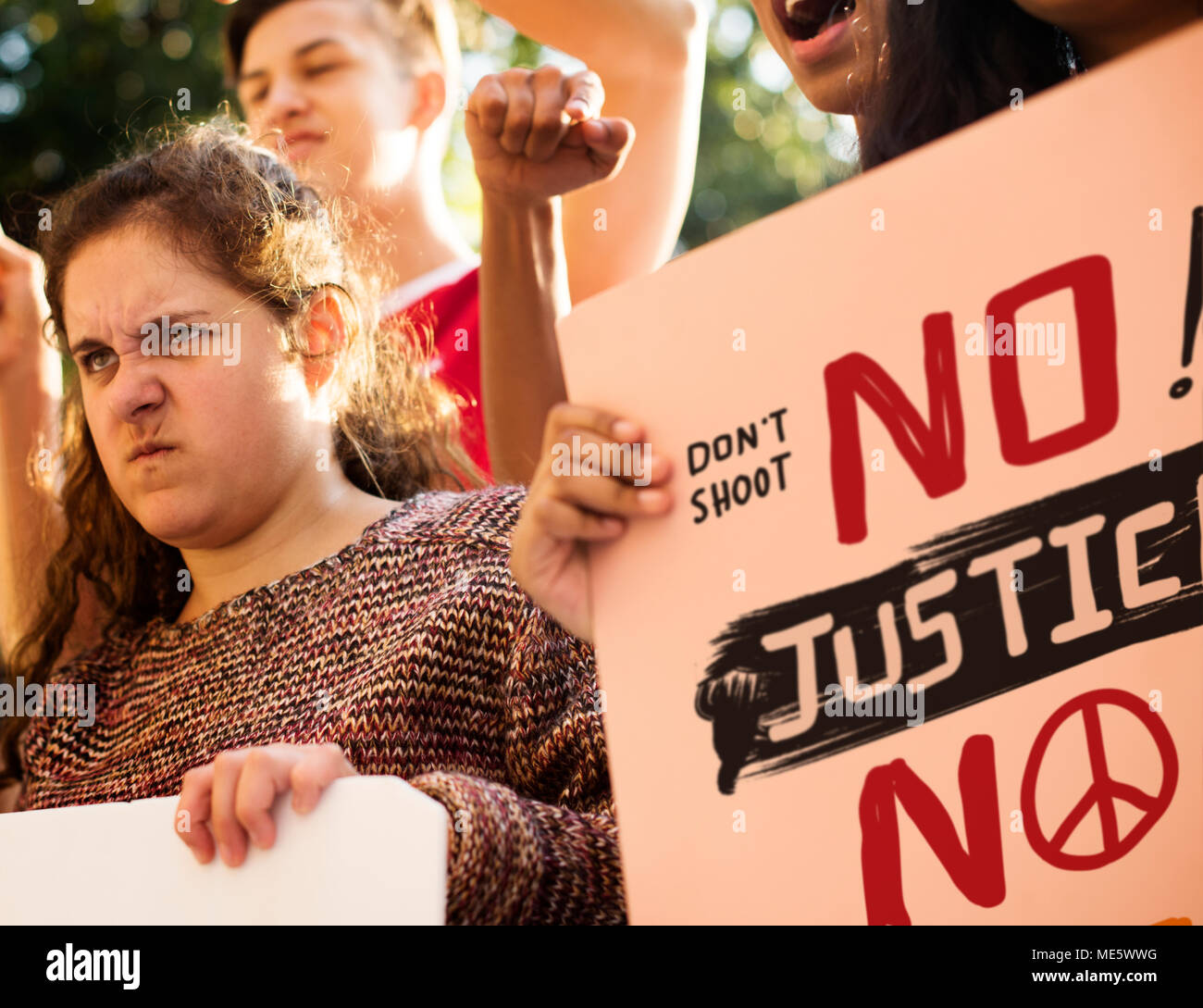 Closeup of angry teen girl protesting demonstration holding posters antiwar justice peace concept - Stock Image