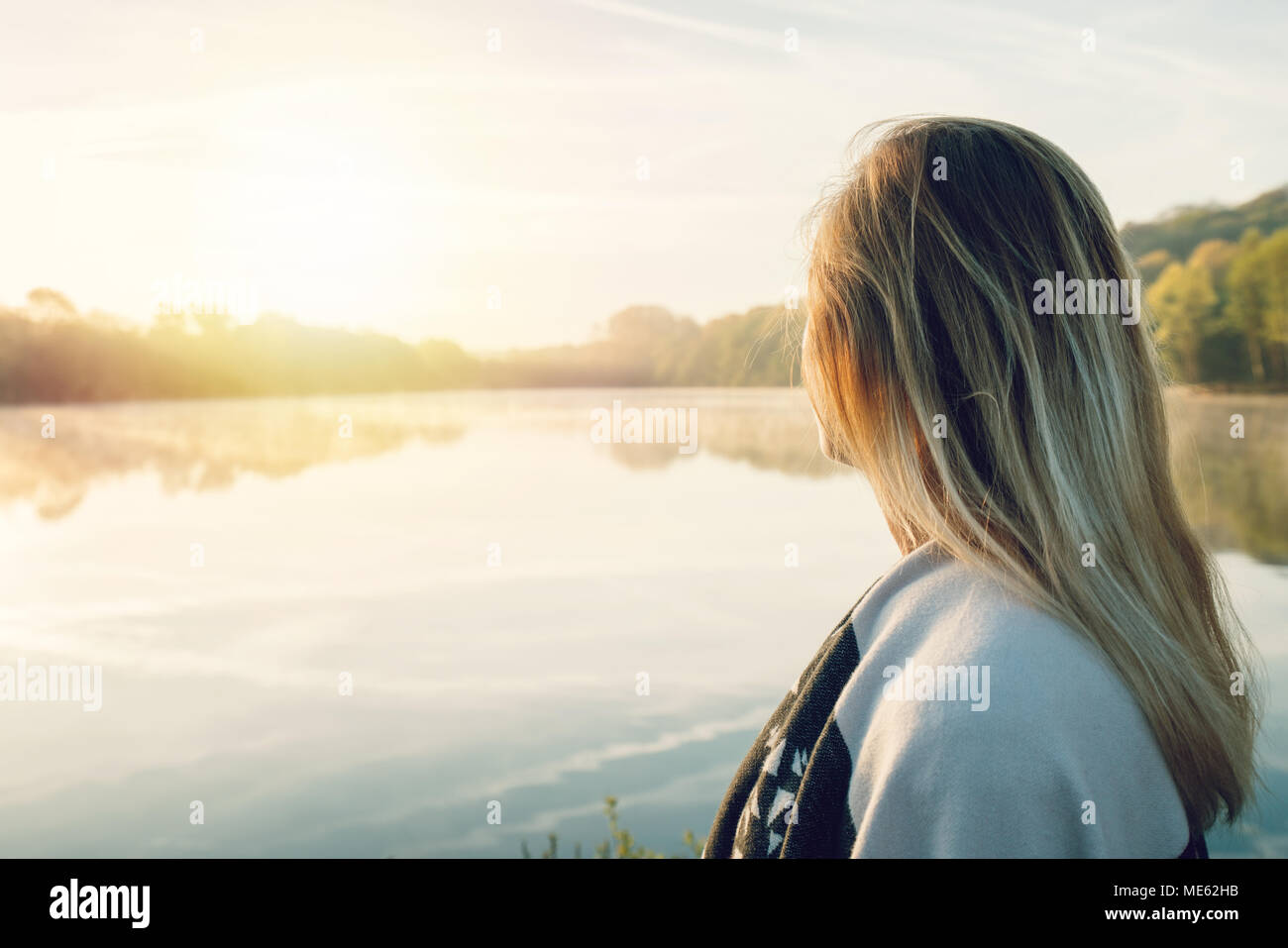 Young woman contemplating nature by the lake at sunrise, springtime, France, Europe. People travel relaxation in nature concept. Tones image - Stock Image