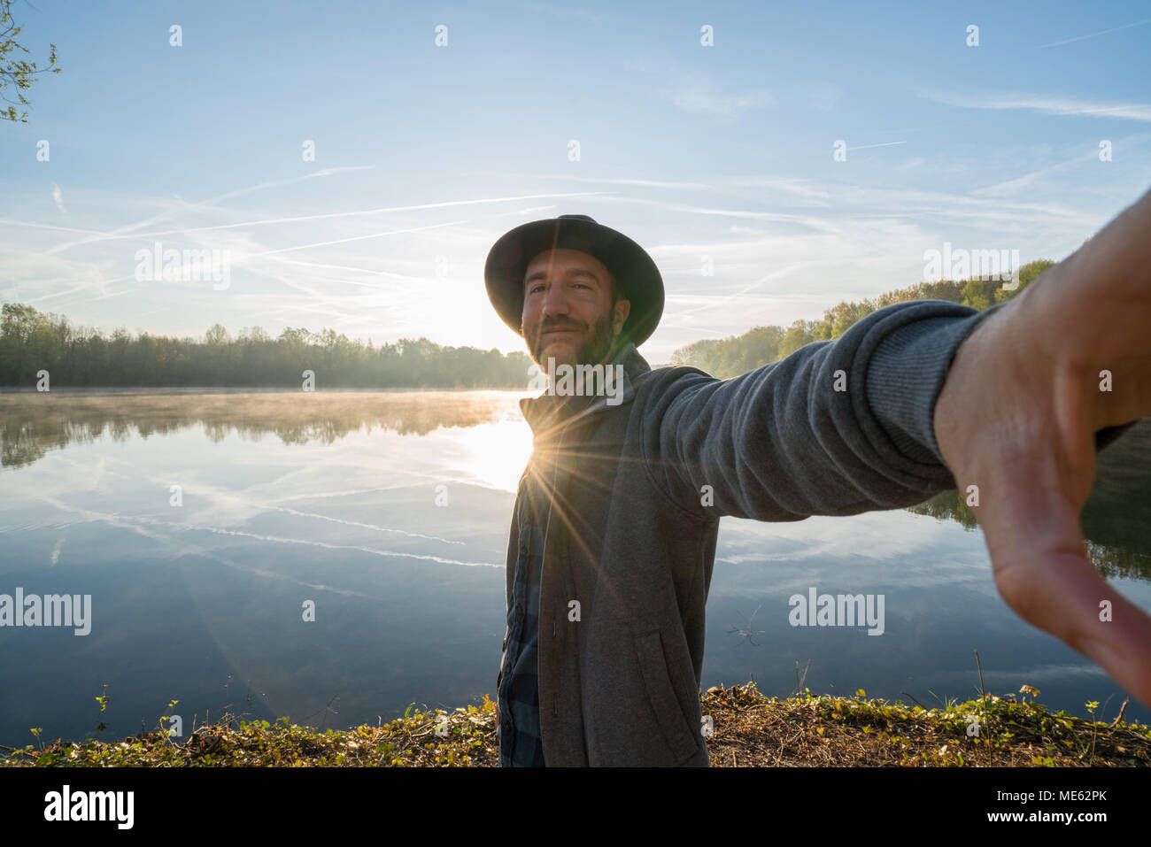 Young man by the lake at sunrise takes a selfie portrait using mobile phone, beautiful reflection on water surface. Travel people concept France Stock Photo