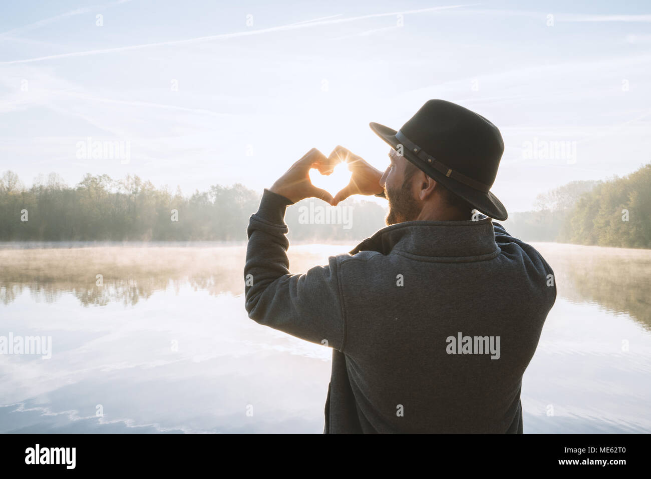 Young man standing by the lake at sunrise making a heart shape finger frame on the beautiful landscape, reflection on water. People love travel Stock Photo