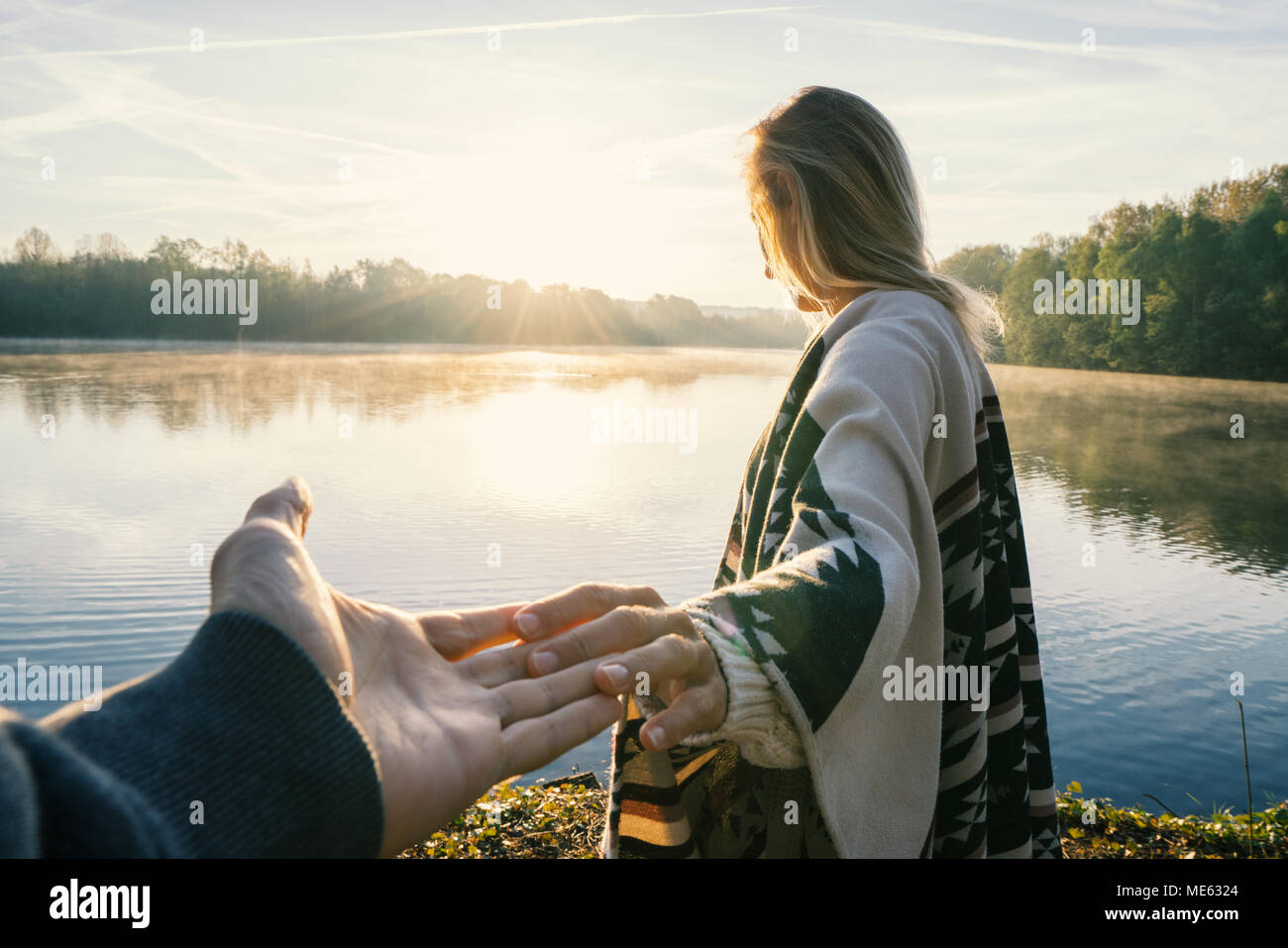 Follow me to concept, Young woman leading boyfriend to the lakeshore at sunrise, holding hands, People travel couple beginning. Shot in France, Europe Stock Photo