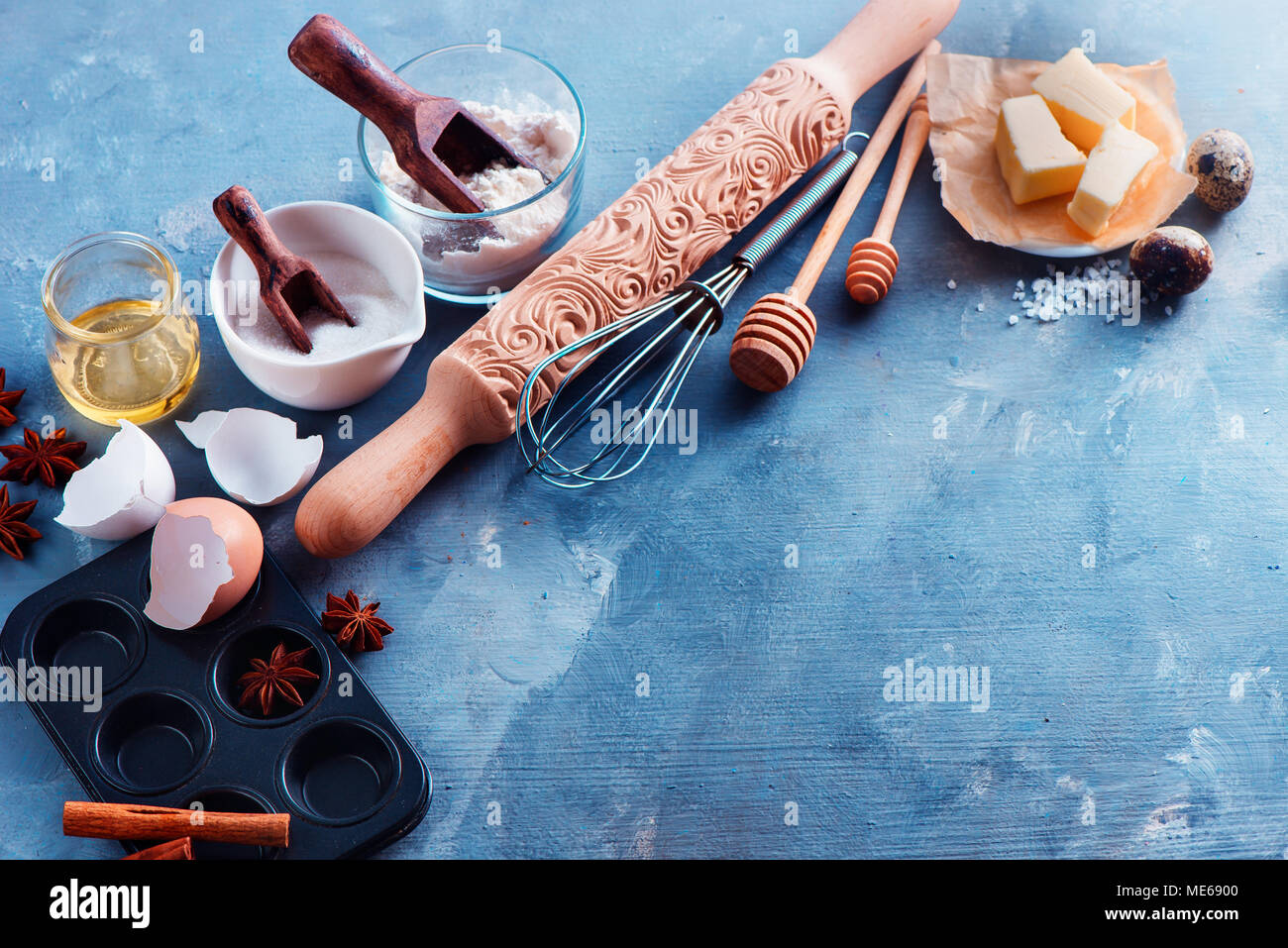 Header with baking ingredients and tools flat lay. Carved rolling pin, muffin tin, whisk and honey spoons in a home cooking concept with copy space. - Stock Image