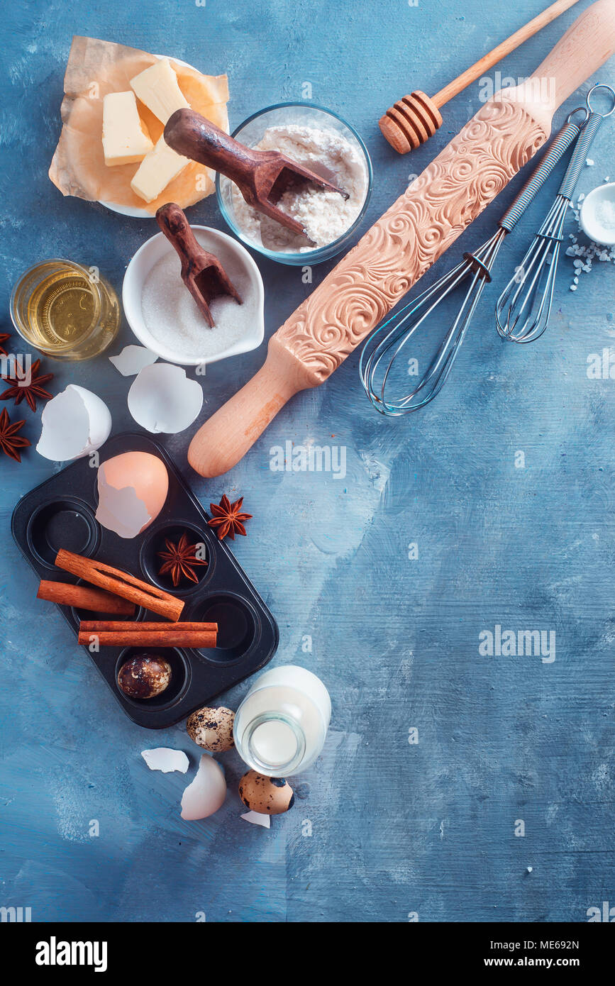 Baking ingredients and tools from above. Carved rolling pin, muffin tin, whisk and honey spoons in a home cooking concept with copy space. - Stock Image