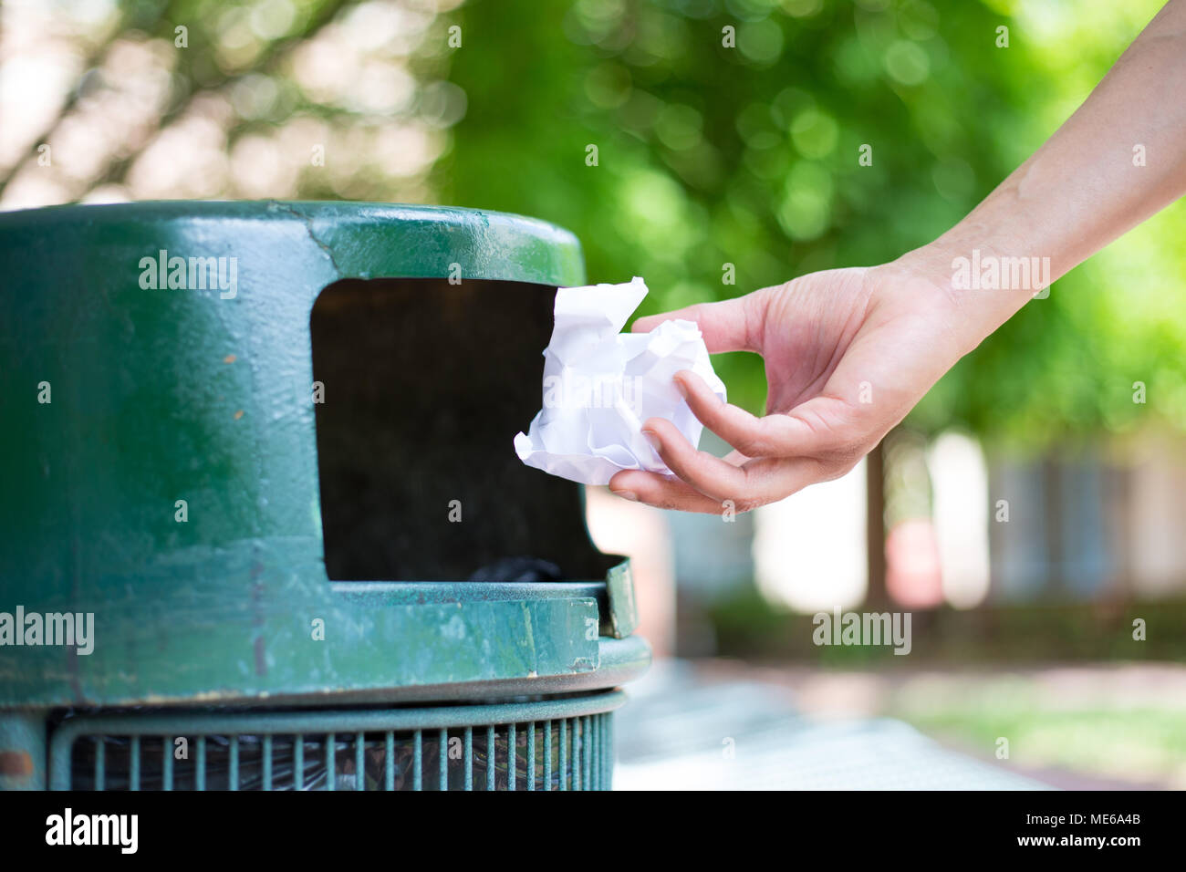Closeup cropped portrait of someone tossing crumpled piece of paper in trash can, isolated outdoors green trees background - Stock Image