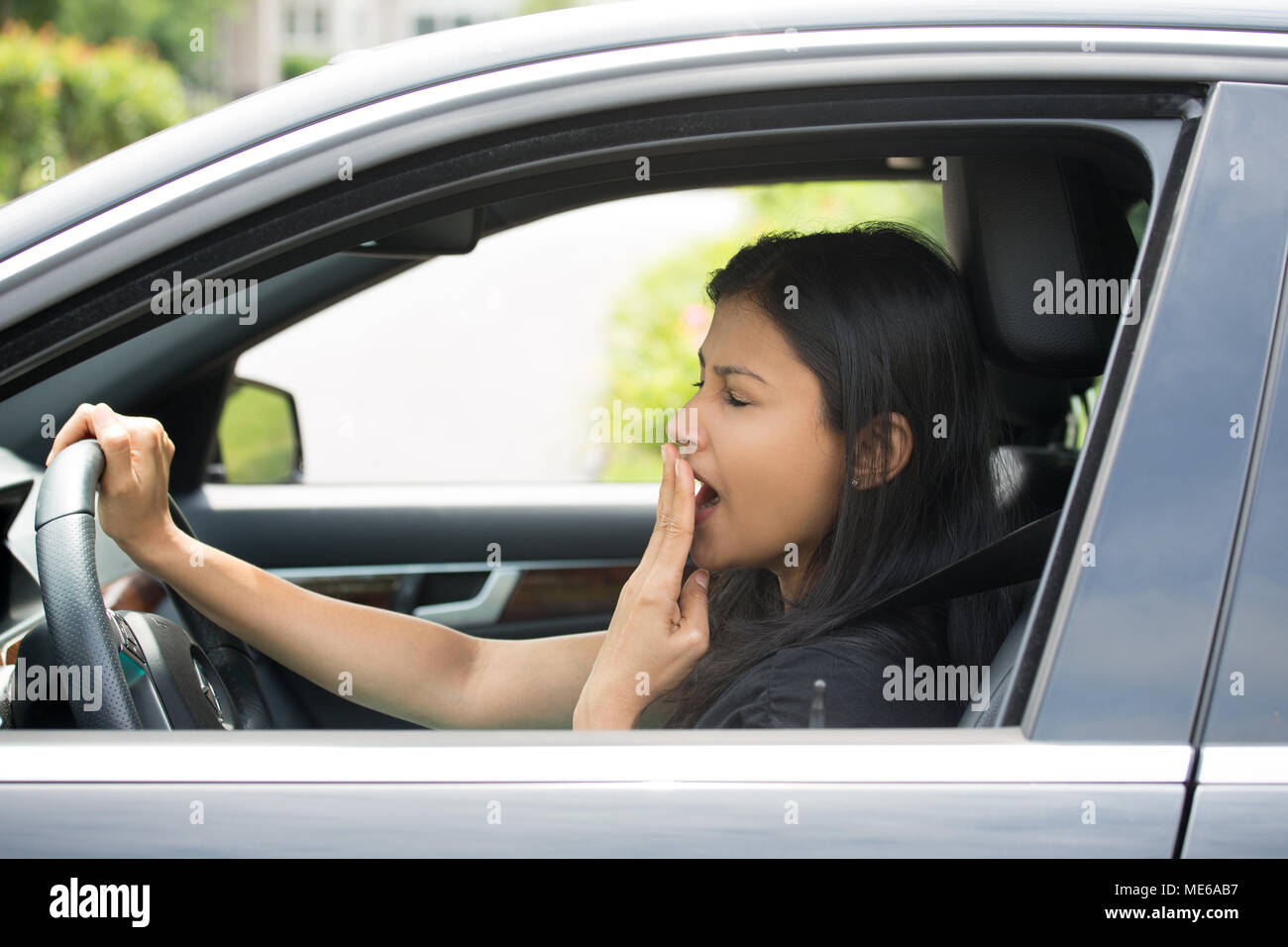Closeup portrait tired young attractive woman with short attention span, driving her car after long hours trip, yawning at wheel, isolated outside bac - Stock Image