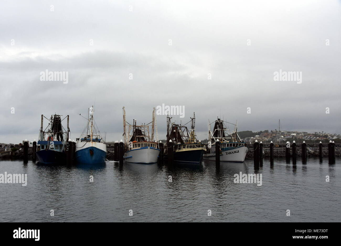 Coffs Harbour, Australia - Dec 31, 2017. Fisher boats at the marina in Solitary Islands Marine Park on a cloudy day. Stock Photo