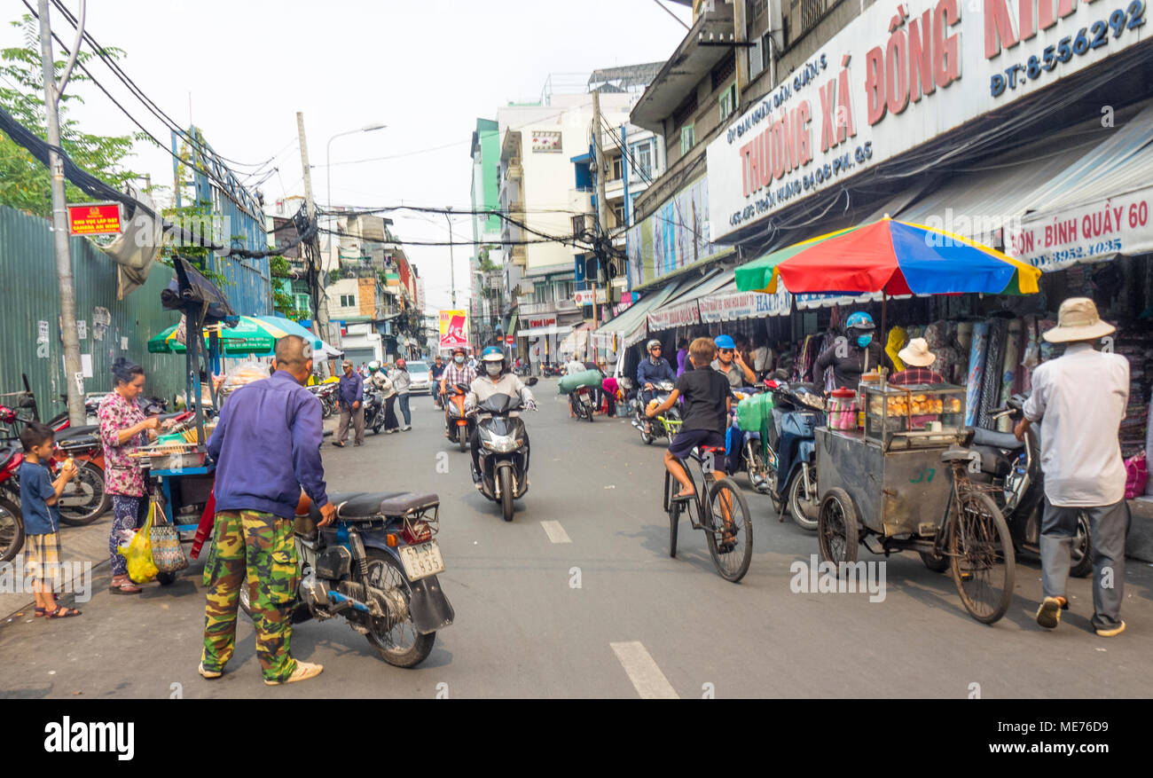 Motorcyclists, cyclists and street vendors sharing the road