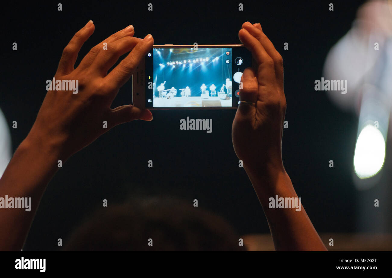 Fan recording a concert with the cellphone - Stock Image