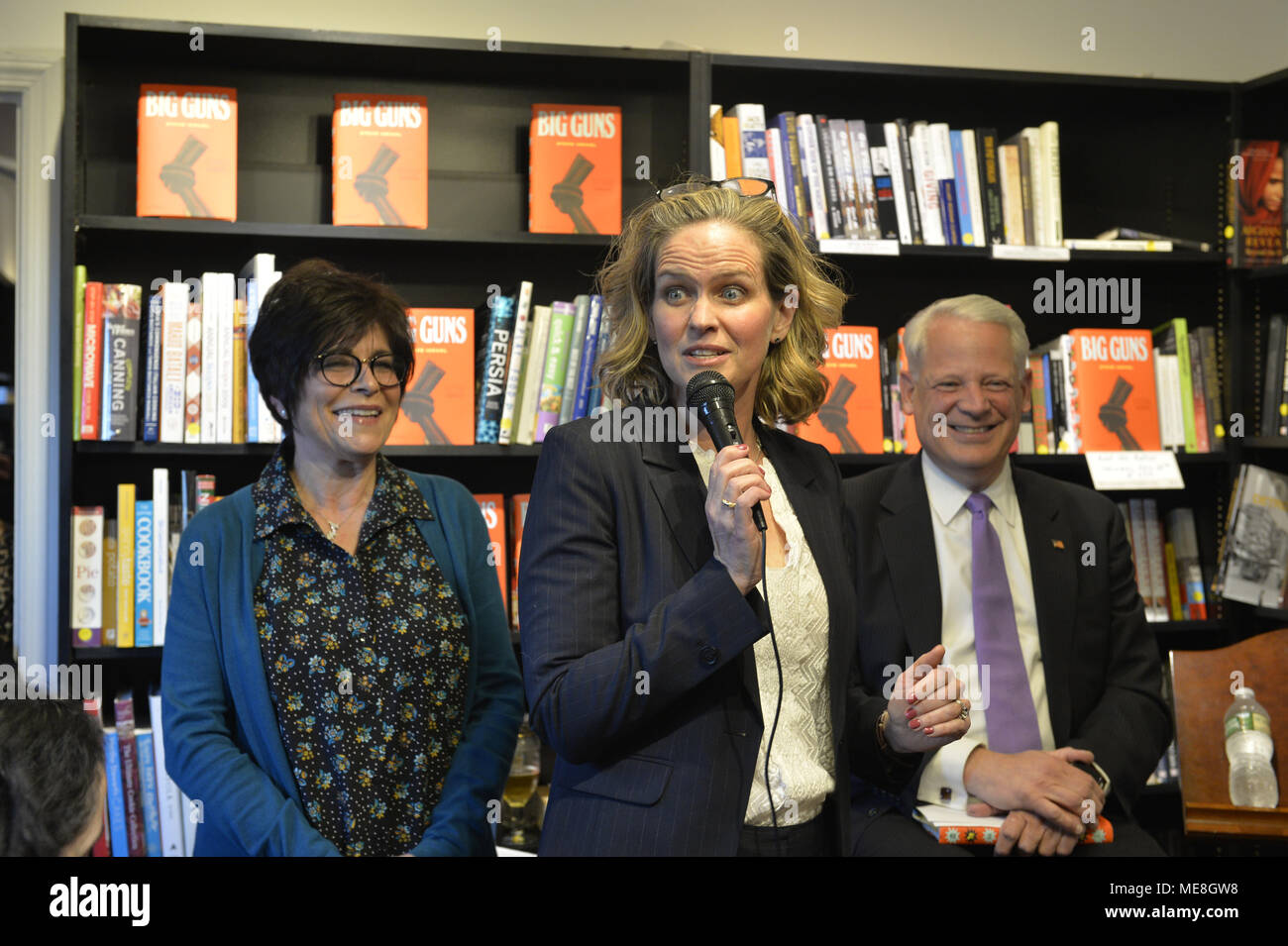 Rockville Centre, New York, USA. 20th Apr, 2018. At center, Nassau County Executive LAURA CURRAN briefly speaks, and L-R, RITA KESTENBAUM and Rep. STEVE ISRAEL smile, at start of special event for Nassau County debut of the former Congressman's (NY - Dem) newest novel BIG GUNS - a satire of the strong gun lobby, weak Congress, and a small Long Island town. Kestenbaum, who was the moderator, is a gun-control activist and former Hempstead Town Councilwoman whose daughter was shot to death at college. Credit: Ann Parry/ZUMA Wire/Alamy Live News - Stock Image