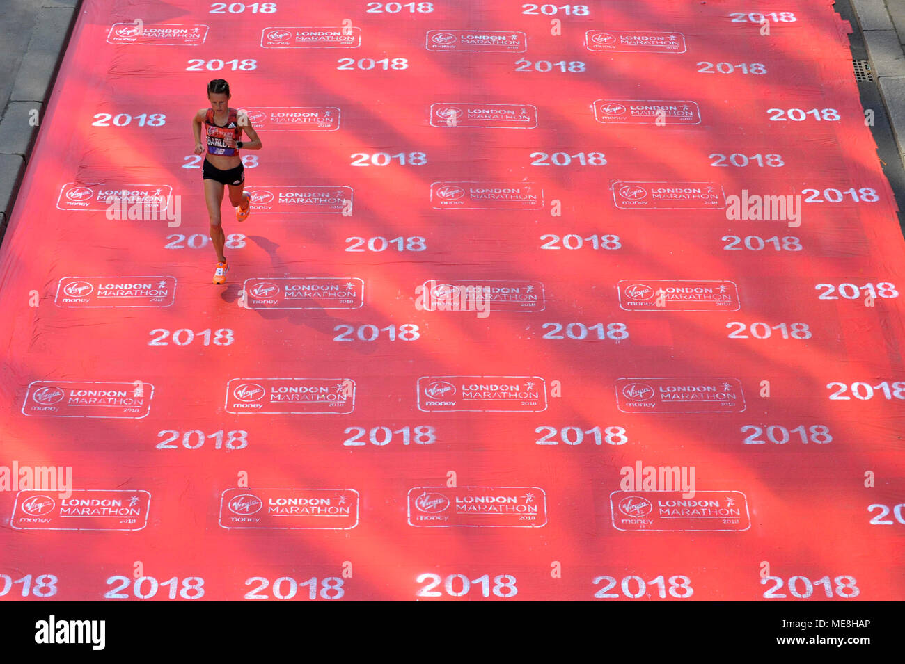 London, UK.  22 April 2018. A runner crosses a red carpet during the 2018 London Marathon. Credit: Stephen Chung / Alamy Live News Stock Photo