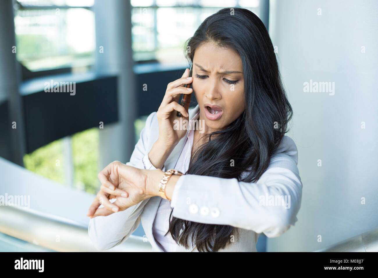 Closeup portrait, young woman in gray business suit blazer talking on cell phone concerned about running out of time on watch, isolated indoors office - Stock Image