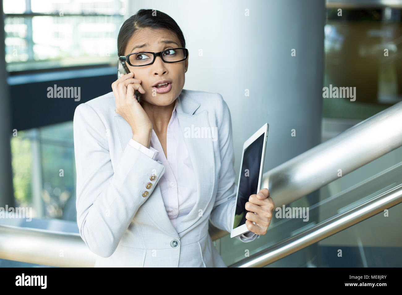 Closeup portrait of pretty busy woman in gray suit and pink shirt holding phone and tablet, sorry and apologizing for her mistakes, caught red-handed, - Stock Image