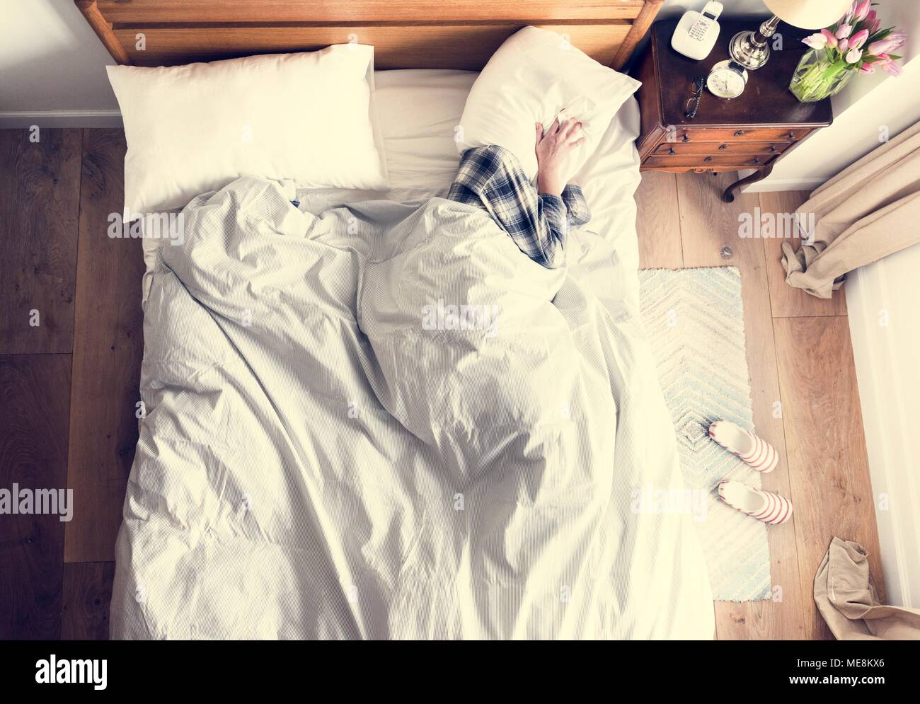 Person on bed insomnia and noise pollution concept - Stock Image