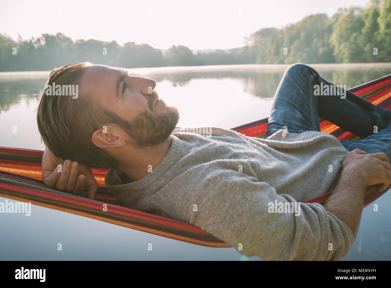 Young man on hammock relaxing by the lake in the morning, sunlight. People travel wellbeing laziness concept. France, Europe Stock Photo