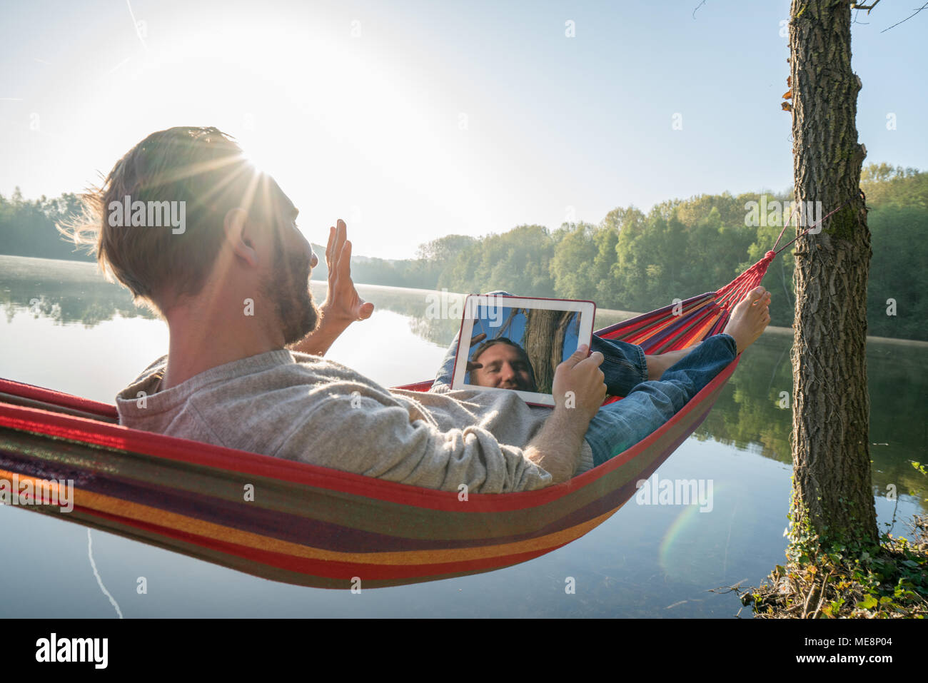 Cheerful young man relaxing on hammock with digital tablet by the lake in the morning, beautiful sunlight. People travel technology relaxation concept Stock Photo