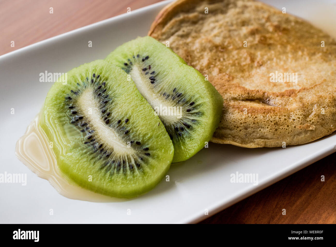 Pancake with kiwi and maple syrup (made with organic flour) homemade product. - Stock Image