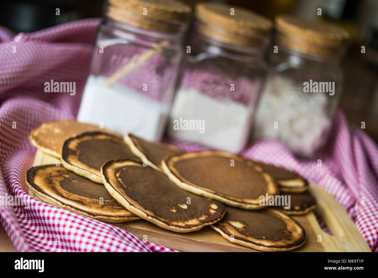 Stack of plain Pancakes on wooden surface - Stock Image