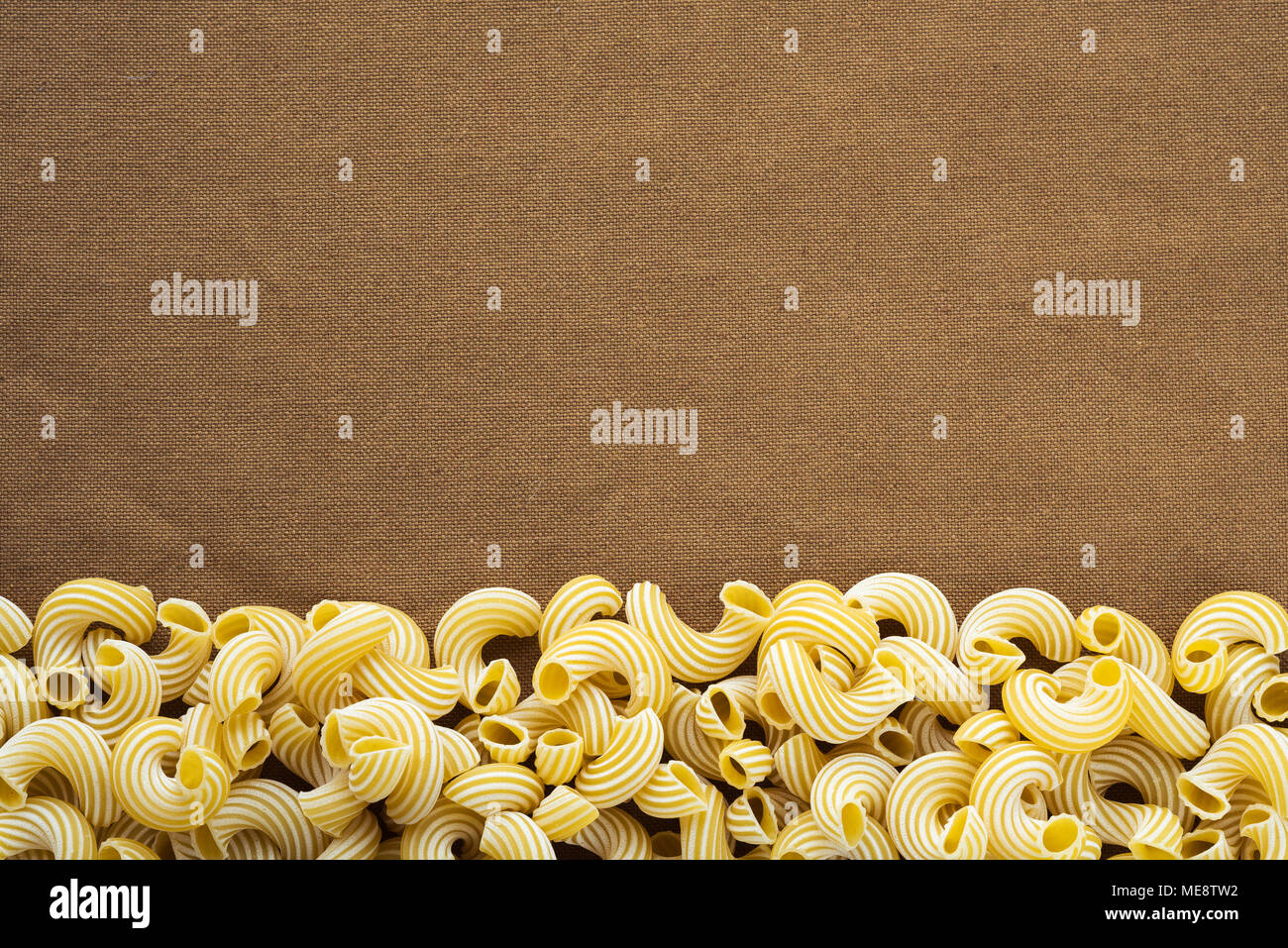 Raw cavatappi Beautiful decomposed pasta from the bottom on a rustic brown  textured background. Close-up view from the top. Free space for text.