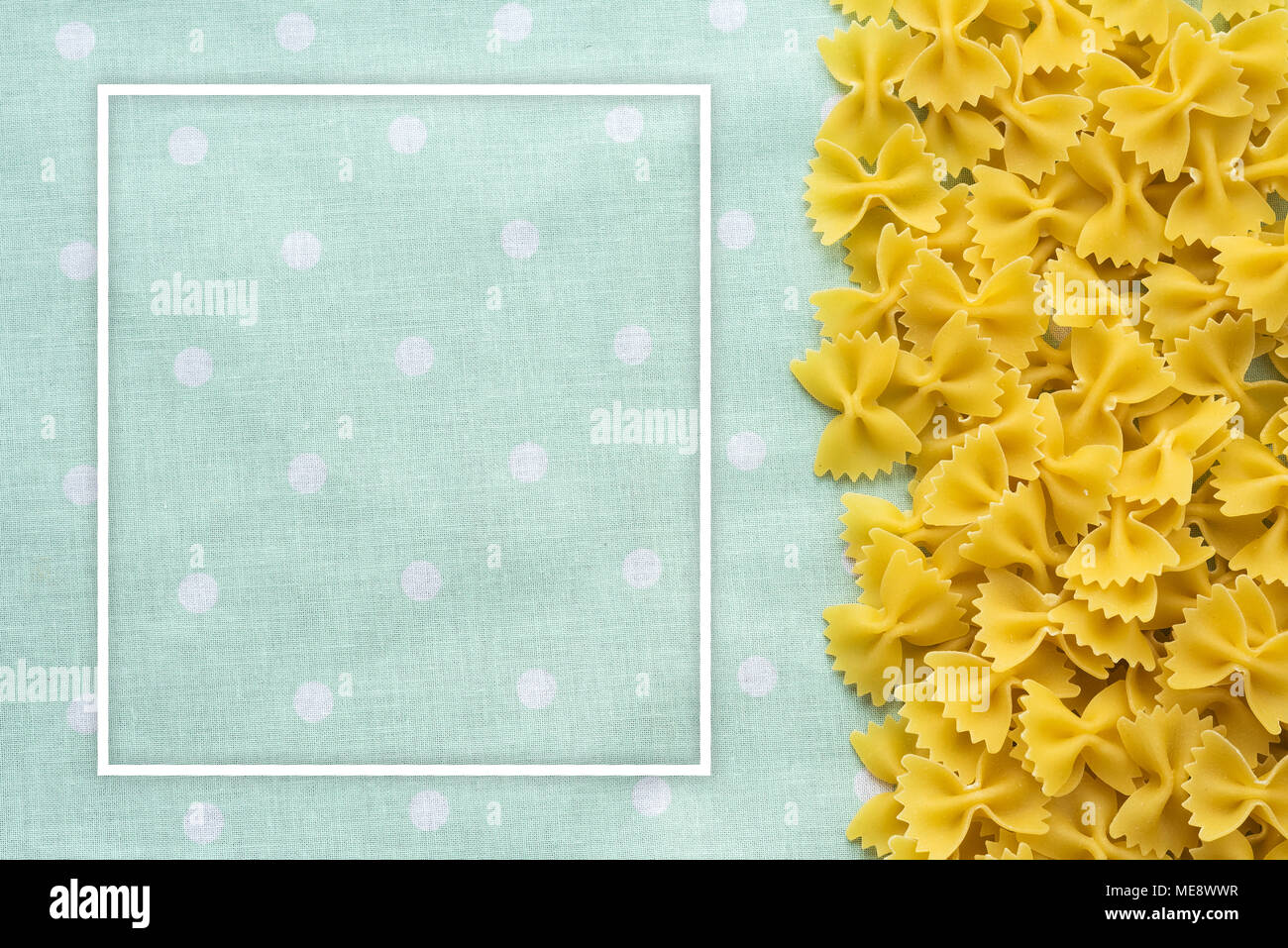 farfalle Raw farfallini Beautiful decomposed pasta with the right, from the side to the green peas texture. Close-up view from the top. With white fra - Stock Image