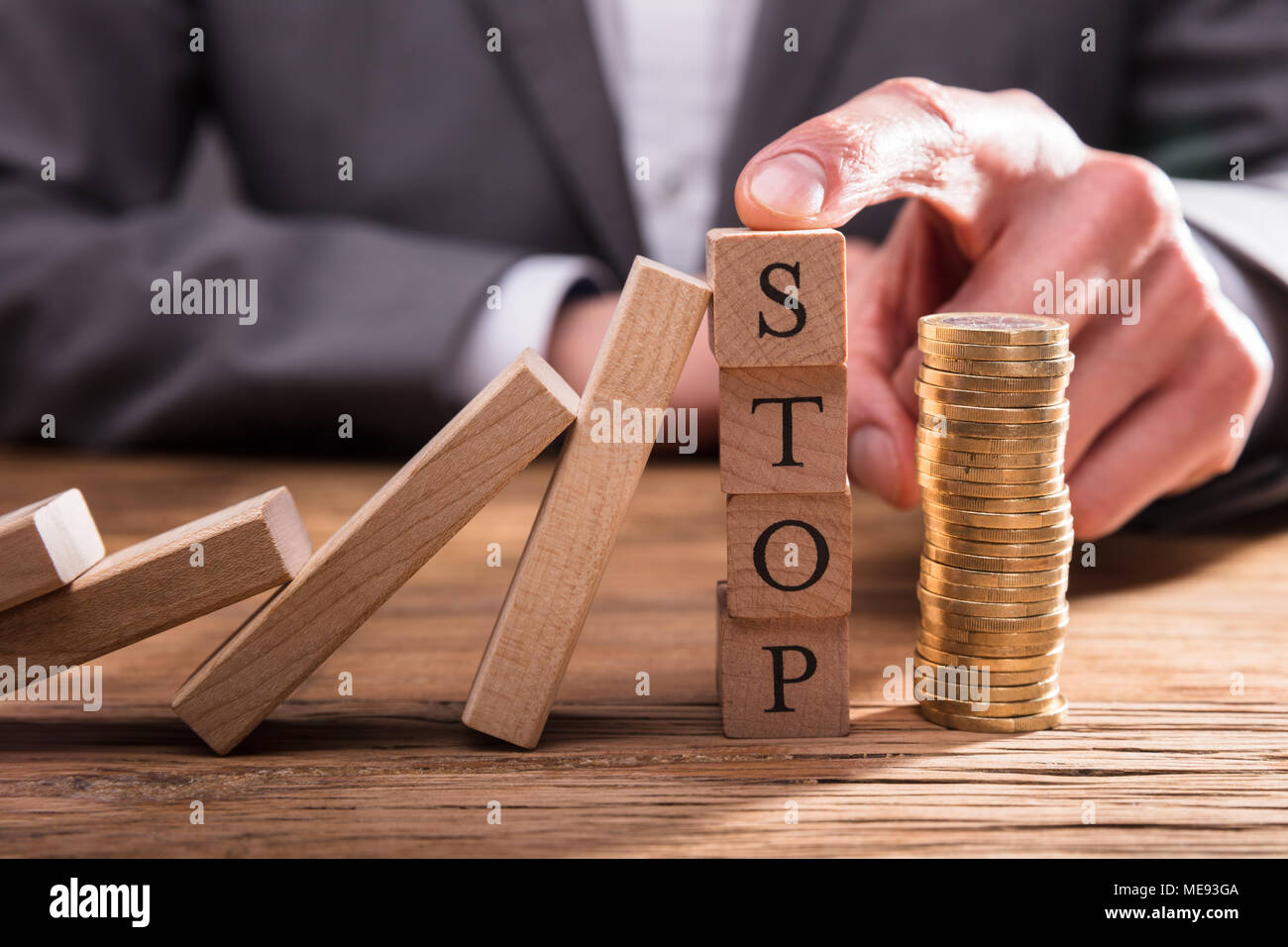 Human Finger Stopping Dominos From Falling With Stacked Coins On Wooden Desk - Stock Image
