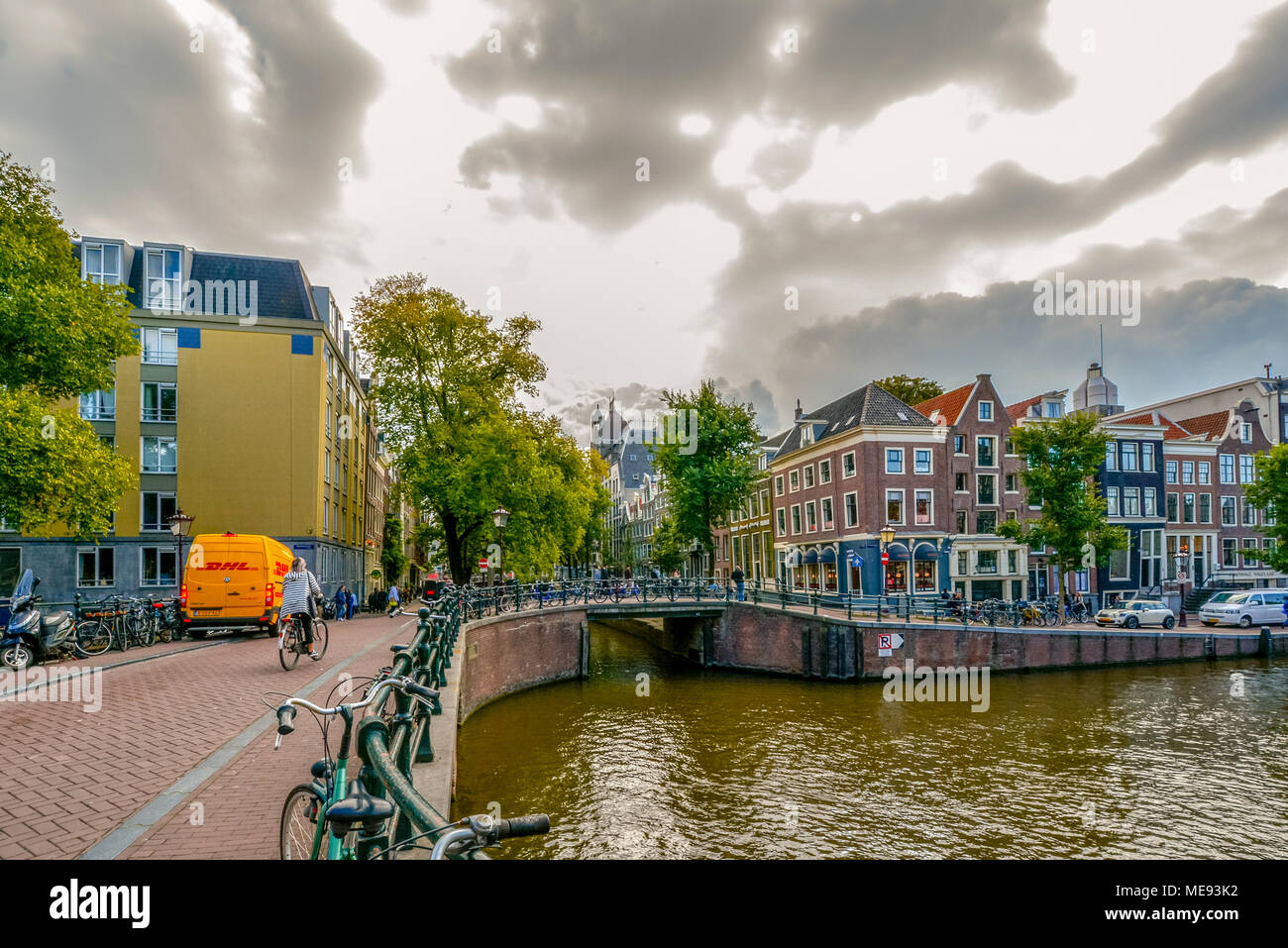 A Dutch woman rides her bike across a bridge over a canal on an overcast autumn day in Amsterdam Netherlands - Stock Image