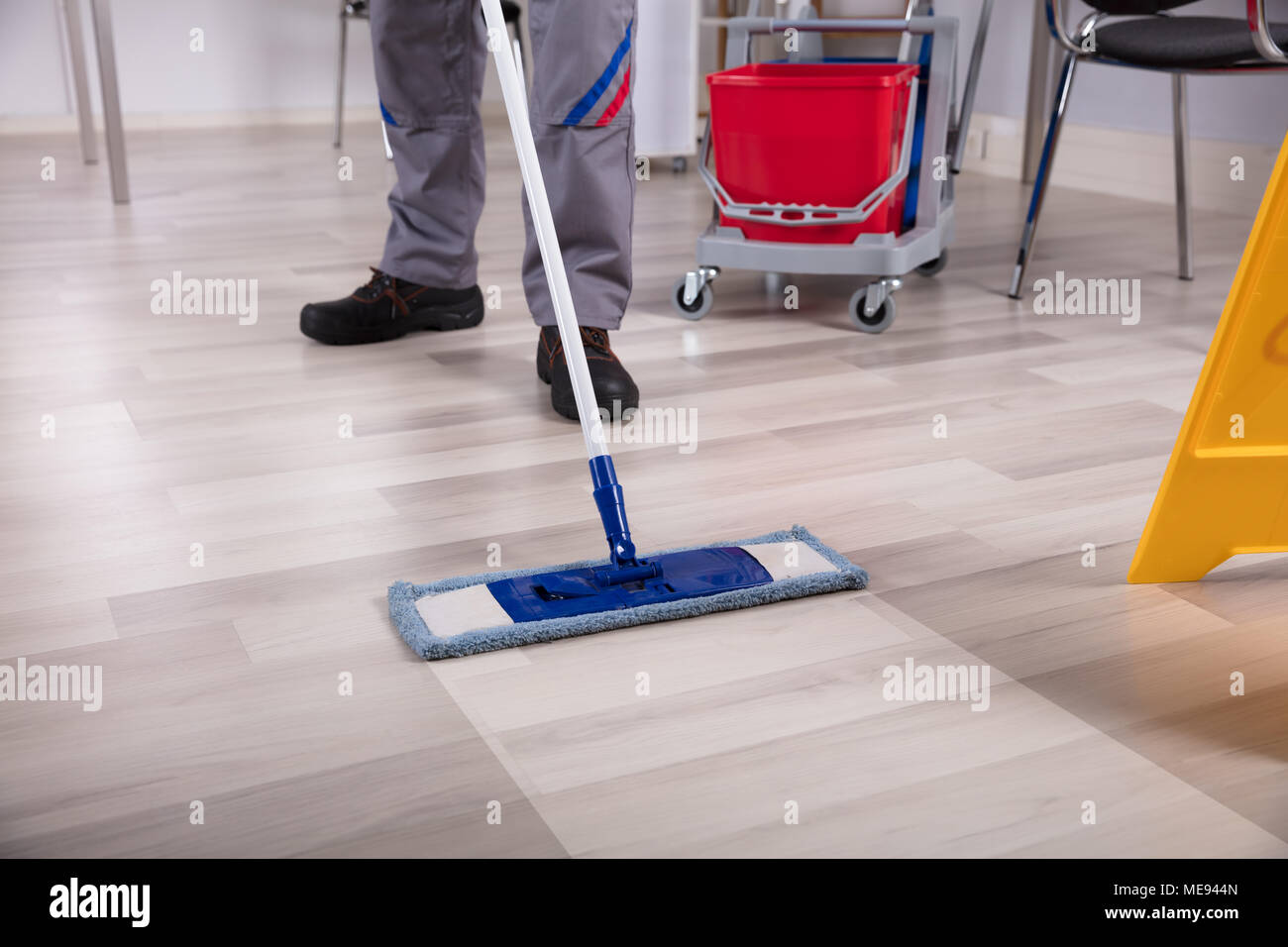 Cleaner Cleaning Hardwood Floor With Mop At Workplace - Stock Image
