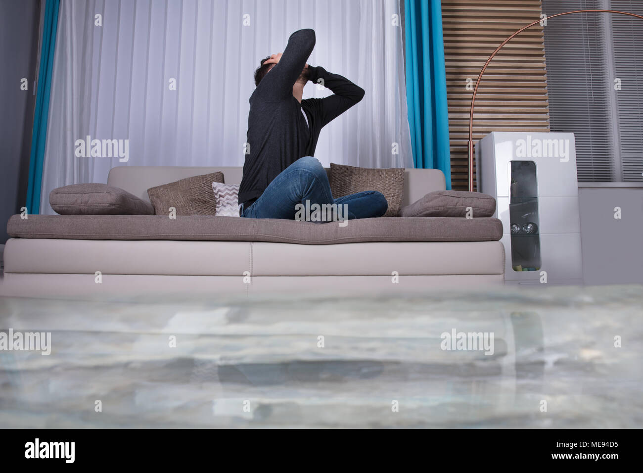 Upset  Man On Sofa With Hands On Head In Room Flooded With Water - Stock Image