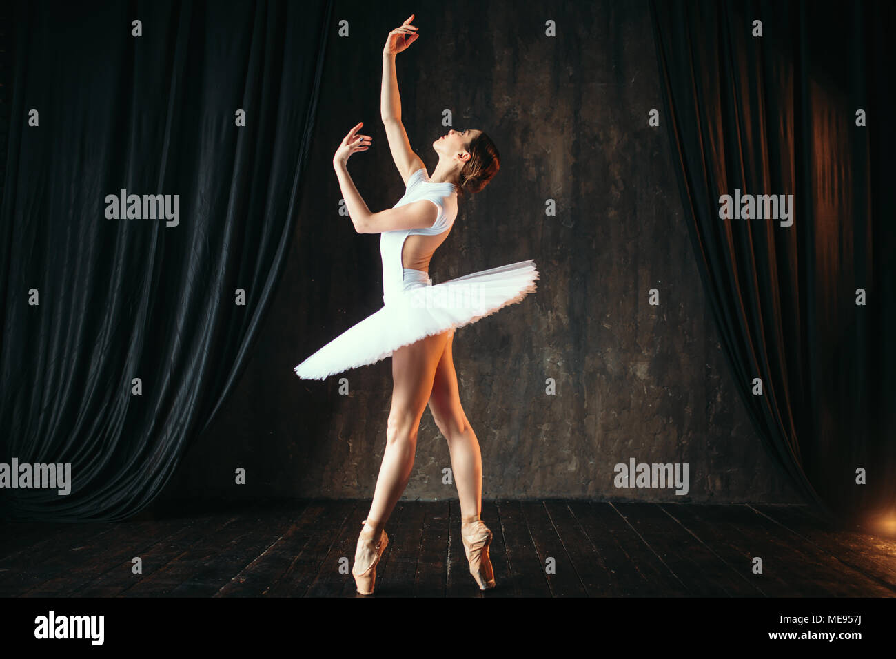 Beautiful graceful ballerina dancing in class. Ballet dancer training on the stage - Stock Image