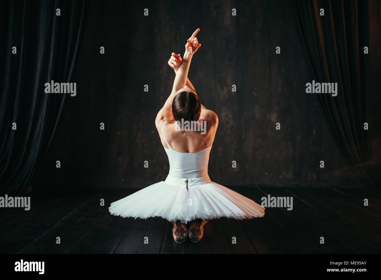 Female classical ballet performer in white dress sitting on the floor, back view. Ballerina training in class with window - Stock Image