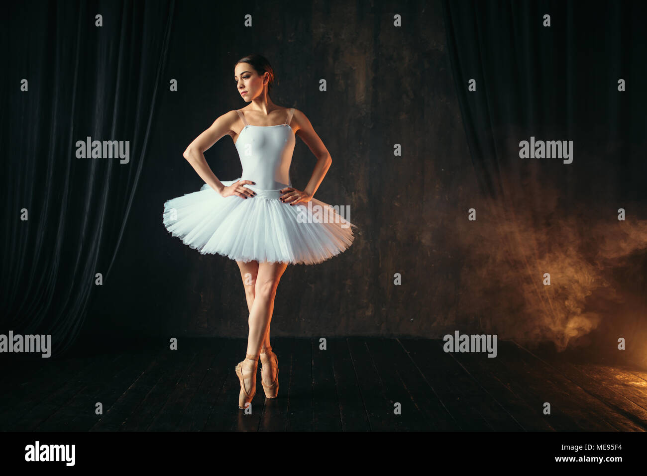Elegance ballerina in white dress and pointe shoes dancing on theatrical stage. Classical ballet dancer training in class - Stock Image