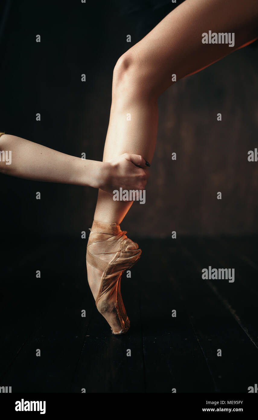 Ballerina hand holds the foot in pointe shoes, black wooden floor. Ballerina in red dress and black practice dancing on the stage in theatre - Stock Image