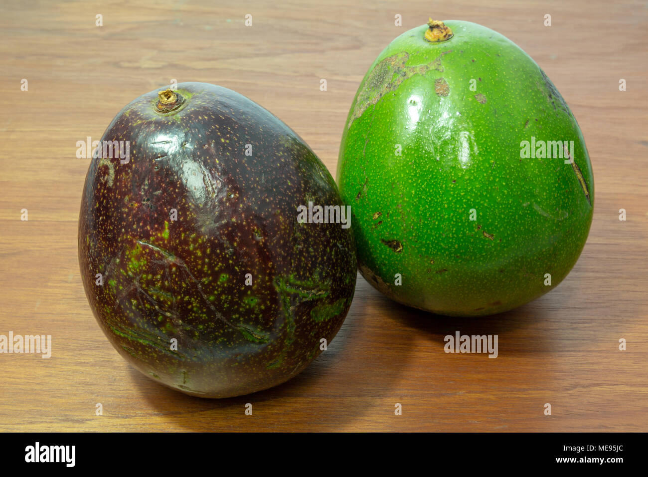 Ripe avocado, one black contrast other green which still ripening, whole and uncut, wooden background - Stock Image