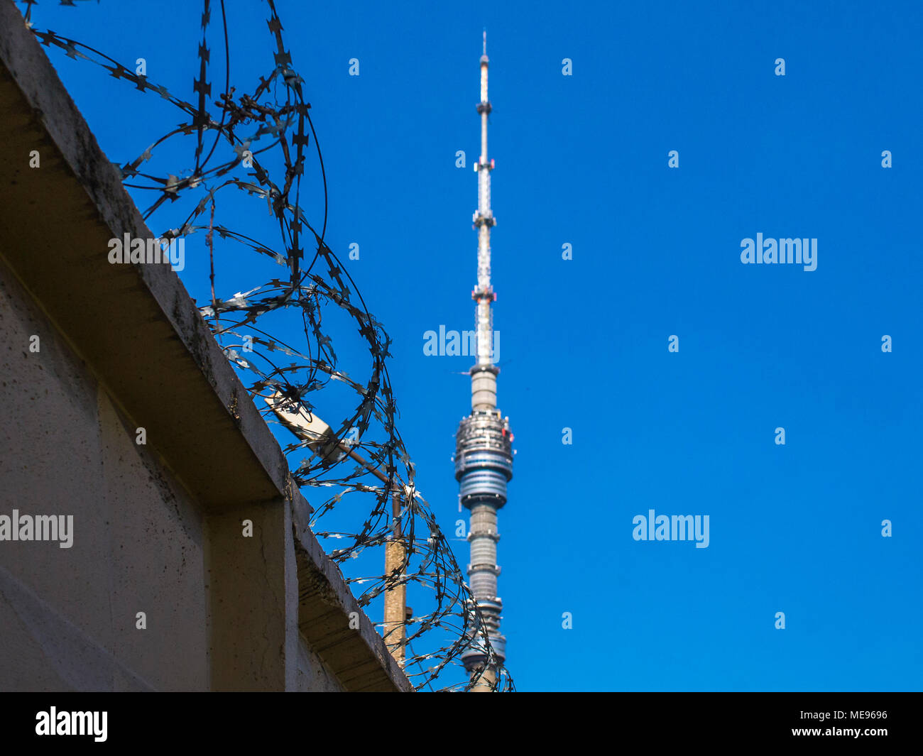 A gray concrete fence with a powerful barbed wire against the backdrop of the Ostankino Tower on a clear, sunny day. Symbolizes the restriction of fre - Stock Image