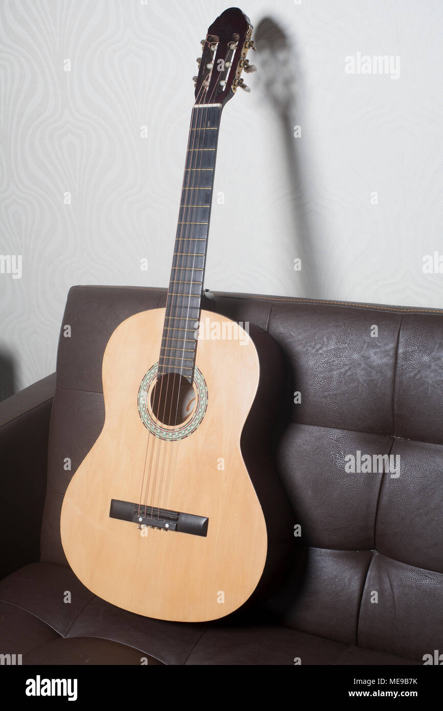 Acoustic classic guitar leaning on a brown leather sofa - Stock Image