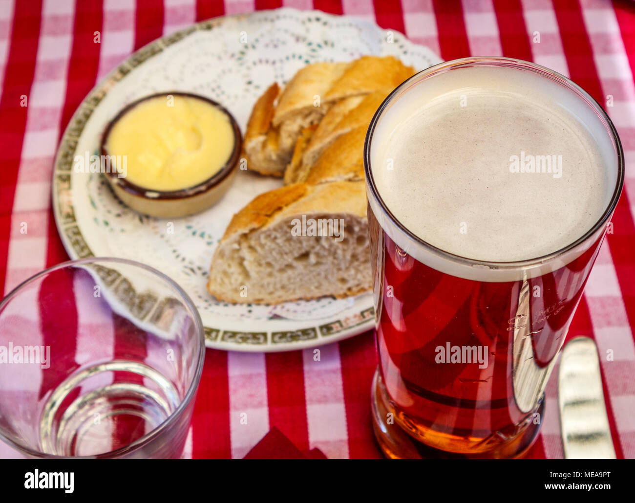 Typical British pub lunch refreshment: a pint of beer in a straight-sided glass with bread and butter on a red and white gingham checked tablecloth - Stock Image