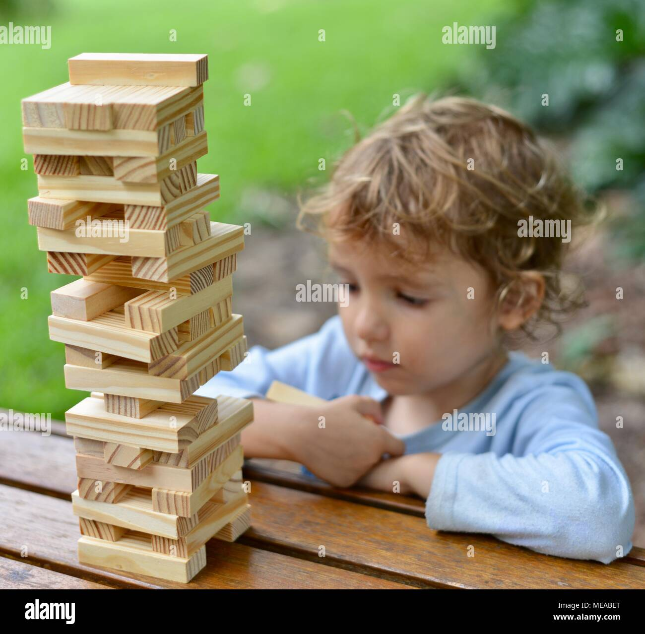 Cute child playing with building blocks and developing fine motor skills and problem solving, Townsville QLD, Australia - Stock Image