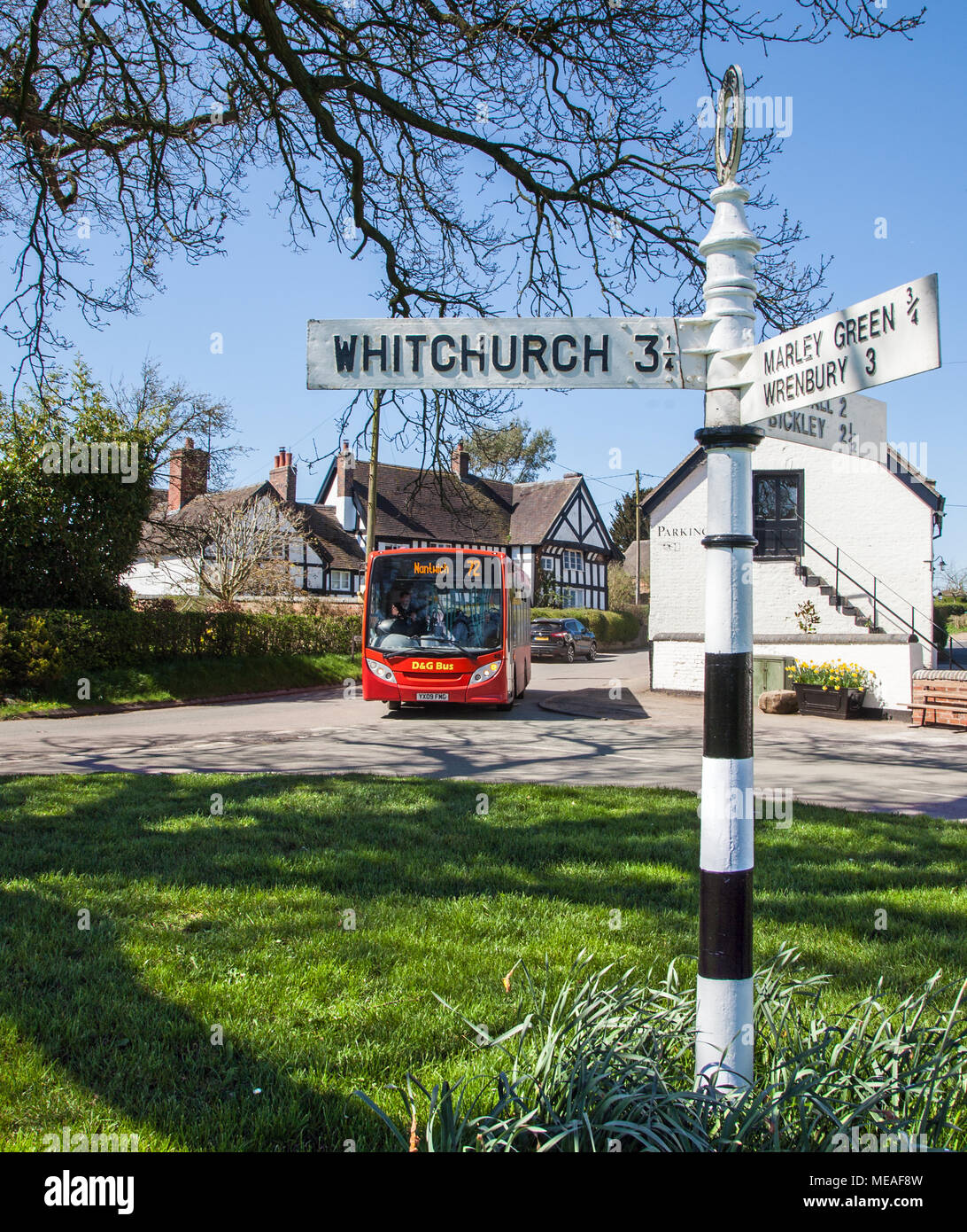 The village green at the South Cheshire rural countryside village of Marbury with and the local country bus service arriving - Stock Image