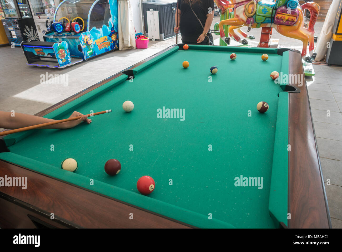 A player lines up a shot on a pool table. - Stock Image