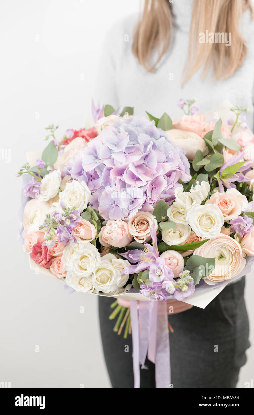 Lilac and light bouquet of beautiful flowers in womens hands lilac and light bouquet of beautiful flowers in womens hands floristry concept spring colors the work of the florist at a flower shop vertical photo izmirmasajfo