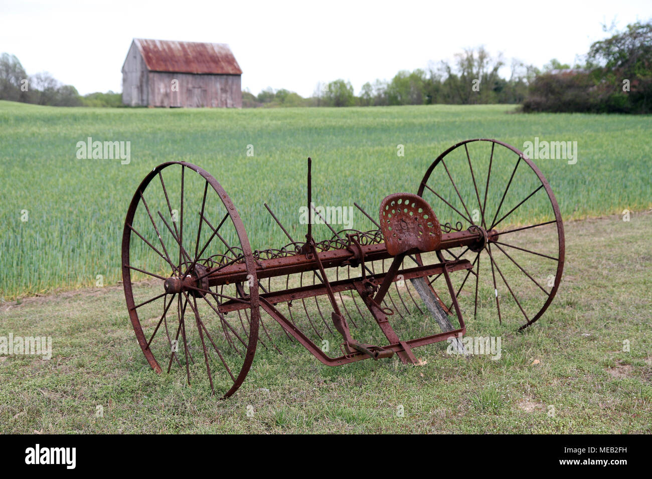 old rusty horse drawn cultivator with farm field and tobacco barn in background - Stock Image