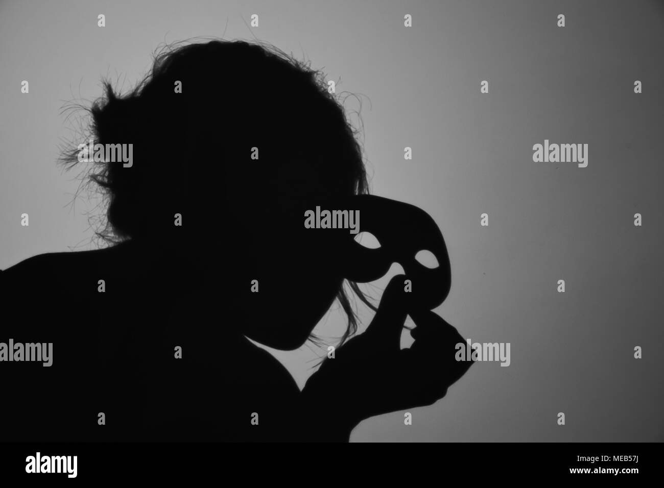 A black and white photography representing a shadow of a female holding a mask. - Stock Image